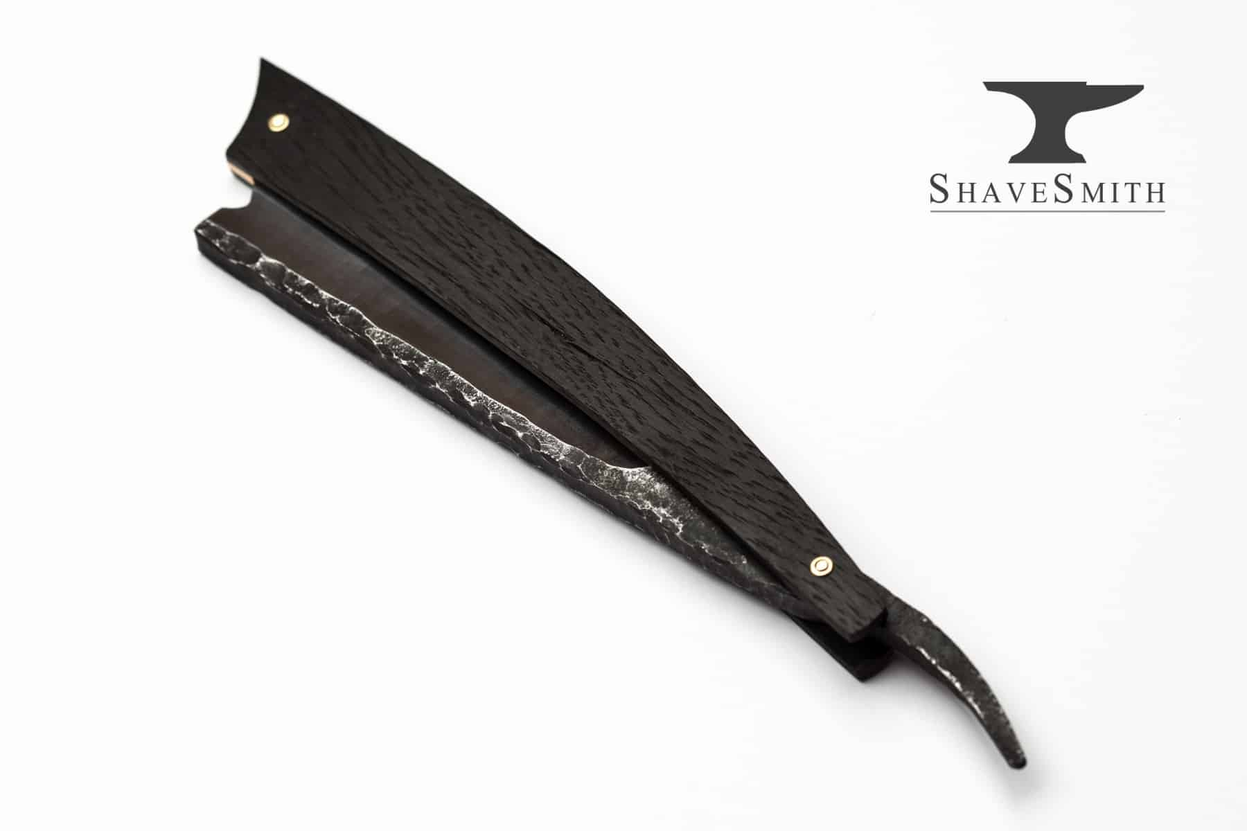 A handmade custom straight razor with ancient bogwood handles, bronze scales, and egravings of galic and nordic origin.
