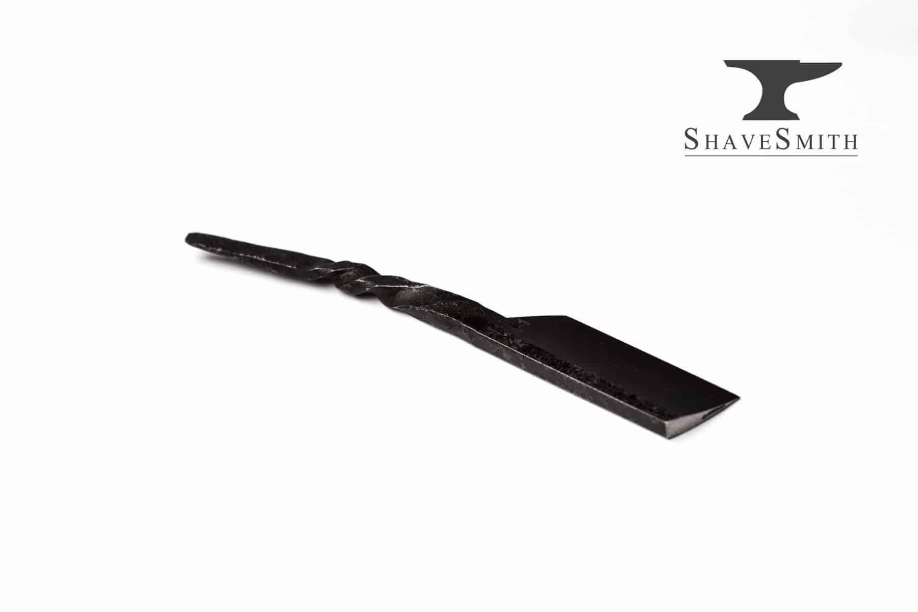 A hand forged custom kamisori razor with twisted handle.